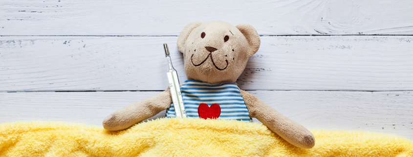 teddy beat tucked into yellow blanket and holding a thermometer