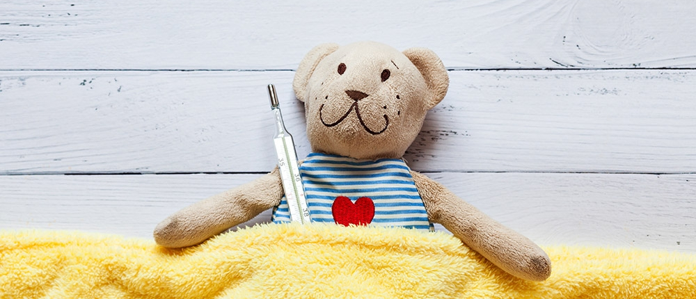teddy bear tucked into yellow blanket and holding a thermometer