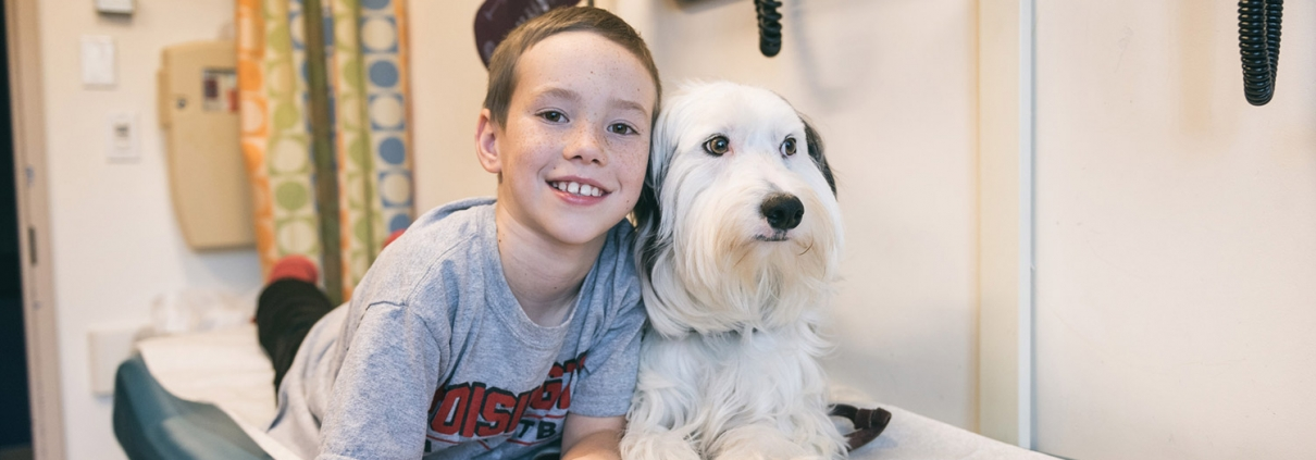boy with dog on examination bed in hospital smiling for camera